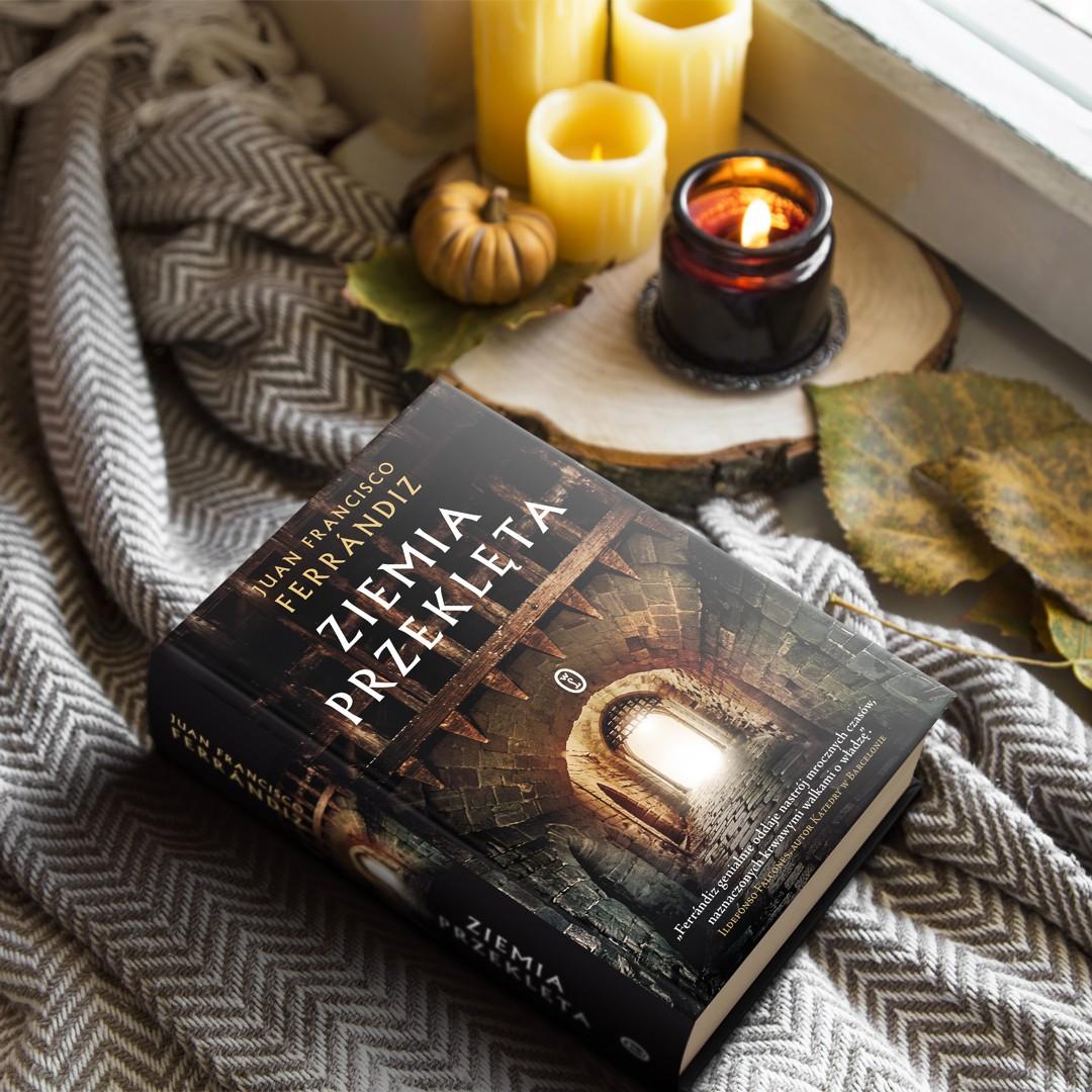 Książka Ziemia Przeklęta na tle swetra i świec
