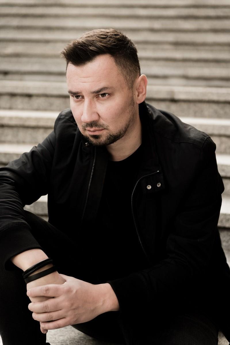 Przemysław Żarski, autor powieści Ślad, pozuje na schodach