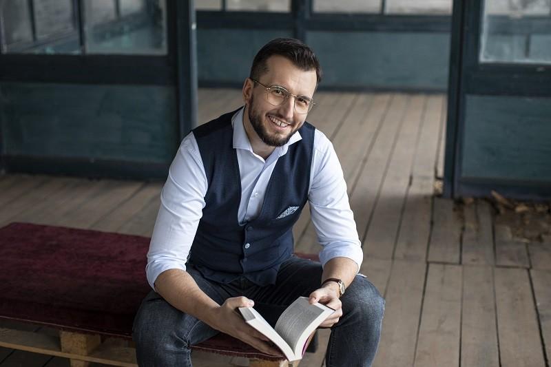 Pisarz Marcin Dudziński ze swoją książką