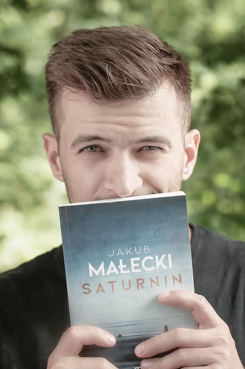 Jakub Małecki z okładką książki