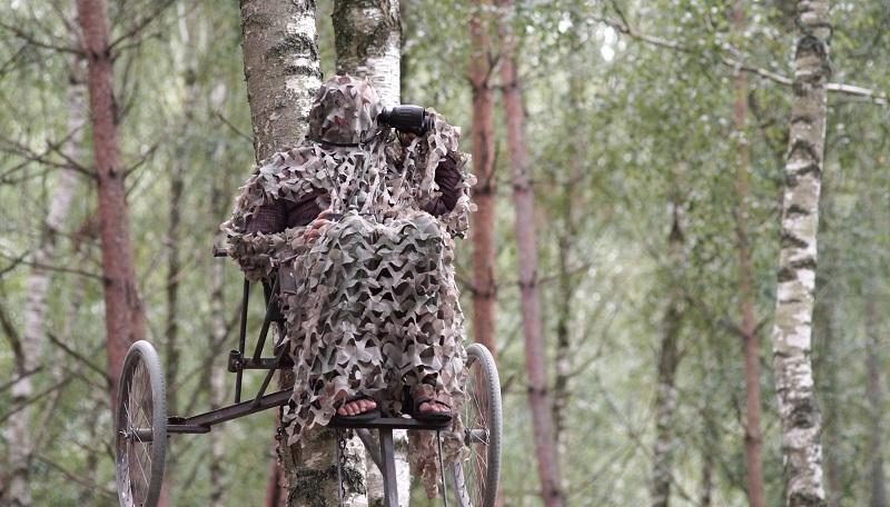 Marcin Kostrzyński w kamuflażu na drzewie obserwuje zwierzęta