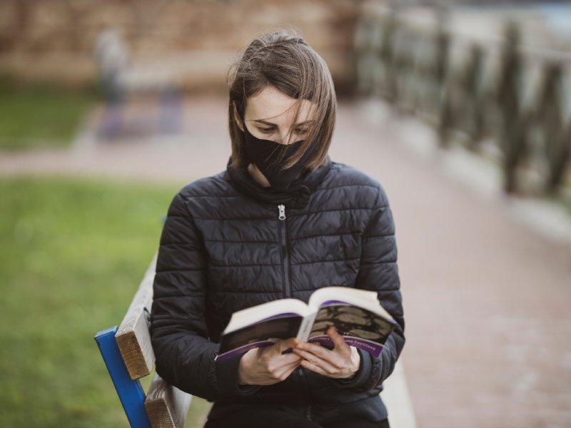 Kobieta w maseczce czyta książkę